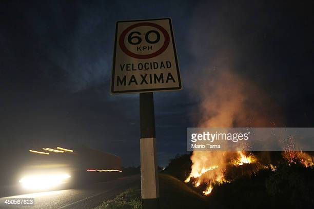 A truck passes as fire burns in a deforested section along the Interoceanic Highway in the Amazon lowlands on November 15 2013 near Puerto Maldonado...