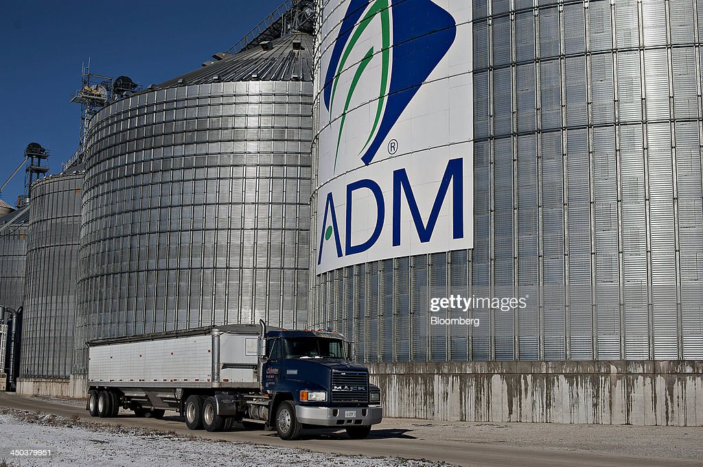 A truck passes in front Archer-Daniels-Midland Co. (ADM) signage displayed on the side of a grain storage bin at an ADM grain elevator in Niantic, Illinois, U.S., on Tuesday, Nov. 12, 2013. Archer-Daniels-Midland Co. procures, transports, stores, processes, and merchandises agricultural commodities and products as well as processes oilseeds, corn, milo, oats, barley, peanuts, and wheat. Photographer: Daniel Acker/Bloomberg via Getty Images