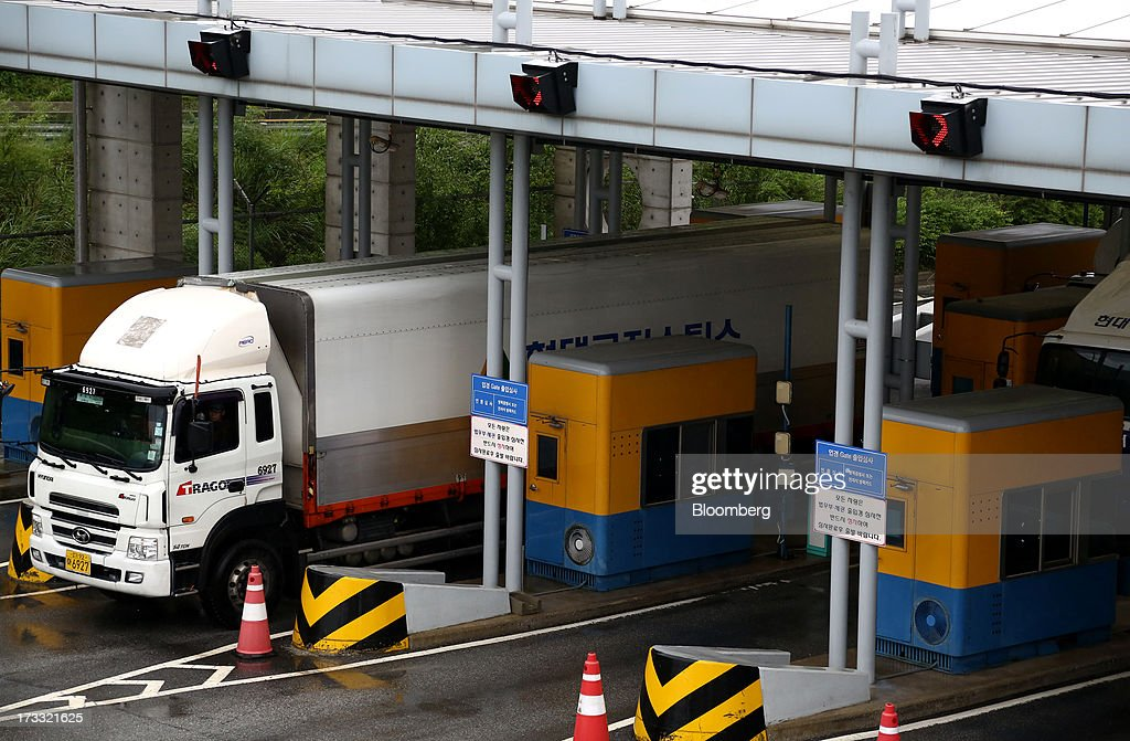 A truck passes through a gate at the Customs, Immigration and Quarantine (CIQ) office as they travel toward the Gaeseong Industrial Complex, on a road linked to North Korea, near the demilitarized zone (DMZ) in Paju, South Korea, on Friday, July 12, 2013. North Korea notified South Korea today that it has deferred two separate sets of talks on the tours and the family reunions it proposed yesterday, and said it wants to focus on the ongoing dialog to reopen the joint Gaeseong industrial zone, the Souths Unification Ministry said in an e-mailed statement. The two sides yesterday decided to hold talks in Gaeseong on July 15, which will be their third round in one week, on normalizing operations in Gaeseong after the North unilaterally recalled its workers in April. Photographer: SeongJoon Cho/Bloomberg via Getty Images