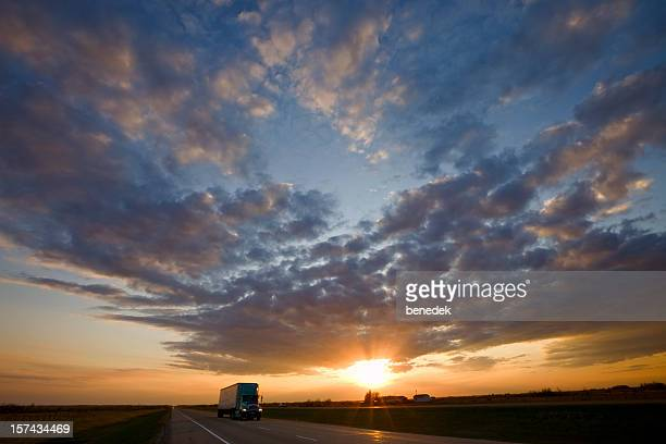 Truck passing by on highway during a glorious sunset
