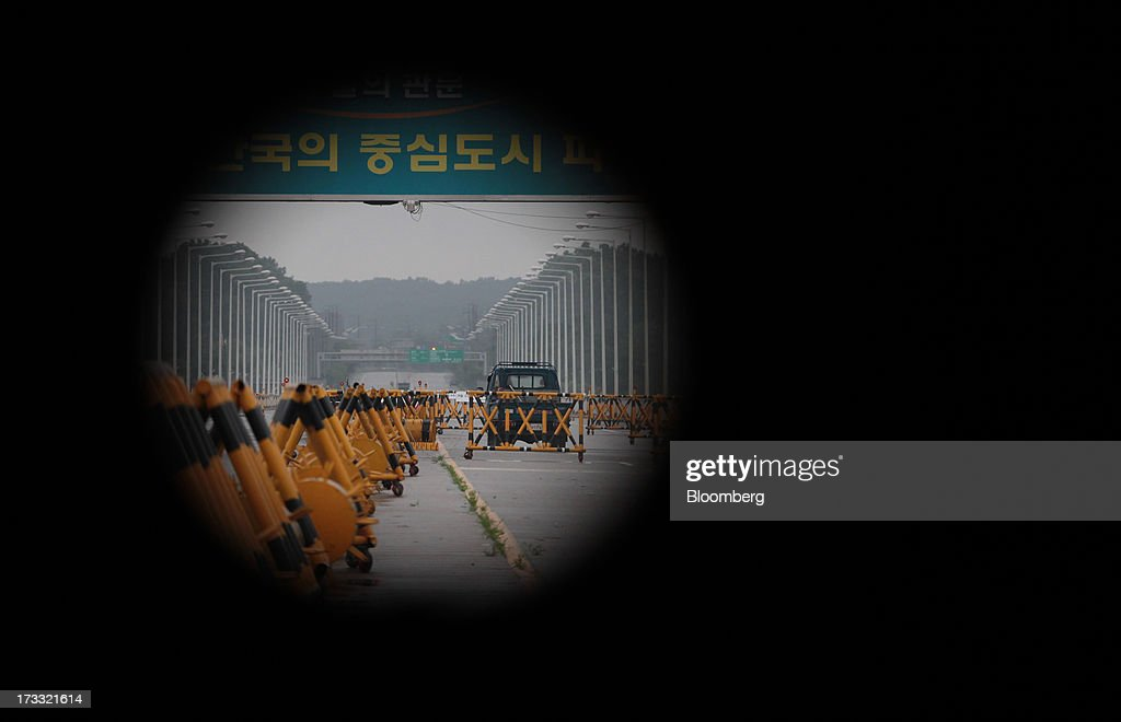 A truck passing through a military check point as it travels toward Gaeseong Industrial Complex is seen through a barricade hole on the Unification Bridge, linked to North Korea, near the demilitarized zone (DMZ) in Paju, South Korea, on Friday, July 12, 2013. North Korea notified South Korea today that it has deferred two separate sets of talks on the tours and the family reunions it proposed yesterday, and said it wants to focus on the ongoing dialog to reopen the joint Gaeseong industrial zone, the Souths Unification Ministry said in an e-mailed statement. The two sides yesterday decided to hold talks in Gaeseong on July 15, which will be their third round in one week, on normalizing operations in Gaeseong after the North unilaterally recalled its workers in April. Photographer: SeongJoon Cho/Bloomberg via Getty Images