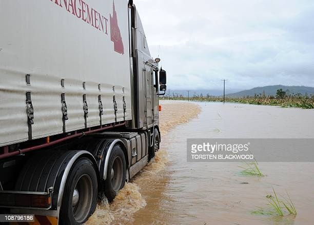 A truck ploughs through flood waters after Cyclone Yasi tore through Tully on February 3 2011 Australia's worst cyclone in a century devastated towns...