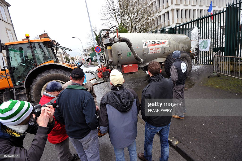 A truck pours water onto a gate in front of the Prefecture in Vendee as demonstrators block a street during a demonstration to denounce new governmental regulations on nitrate, in the center of La Roche-sur-Yon, on January 16, 2013.