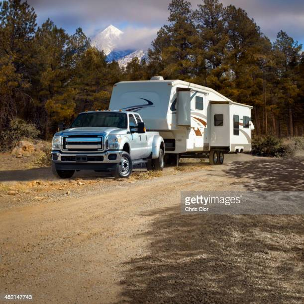 Truck pulling RV trailer on dirt road