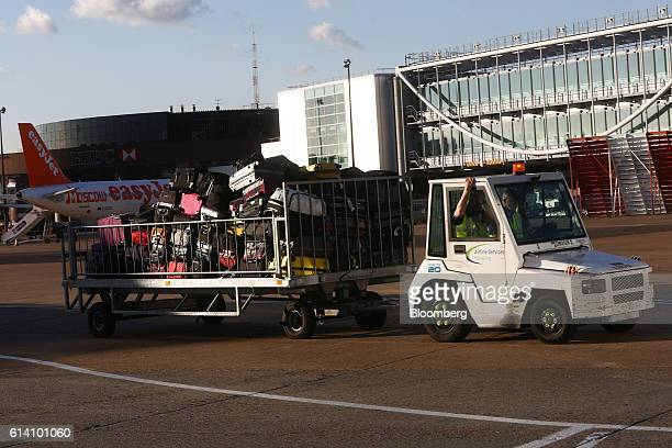 A truck pulls a trailer loaded with luggage at London Gatwick airport in Crawley UK on Tuesday Oct 11 2016 London Mayor Sadiq Khan urged UK Prime...