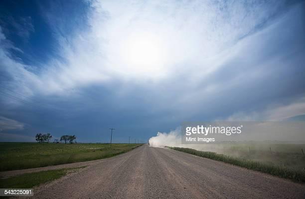 A truck raising dust as it rolls down a prairie road.