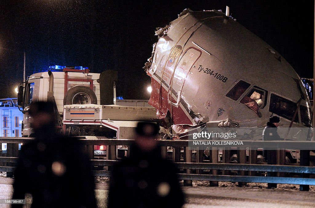 A truck removes the cabin of the Tu-204 jet from its crash site near the Vnukovo airport outside Moscow on December 29, 2012. Four crew were killed when a Russian airliner crashed into a motorway and broke up into three pieces after overshooting the runway at an international Moscow airport. The Red Wings airlines Russian-made Tu-204 jet -- empty of passengers and carrying just its eight crew on a return trip from the Czech Republic -- caught fire after crashing through the perimeter fence of Vnukovo airport in the west of the city. AFP PHOTO / NATALIA KOLESNIKOVA