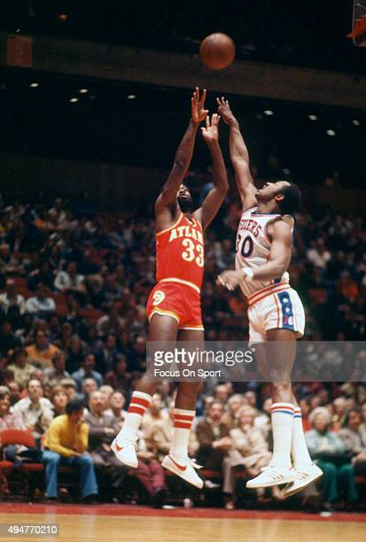 Truck Robinson of the Atlanta Hawks shoots over George McGinnis of the Philadelphia 76ers during an NBA basketball game circa 1977 at The Spectrum in...