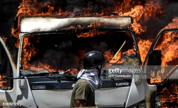 A truck set ablaze by opposition activists blocking an avenue during a protest burns in Caracas on July 18 2017 The Venezuelan opposition called for...
