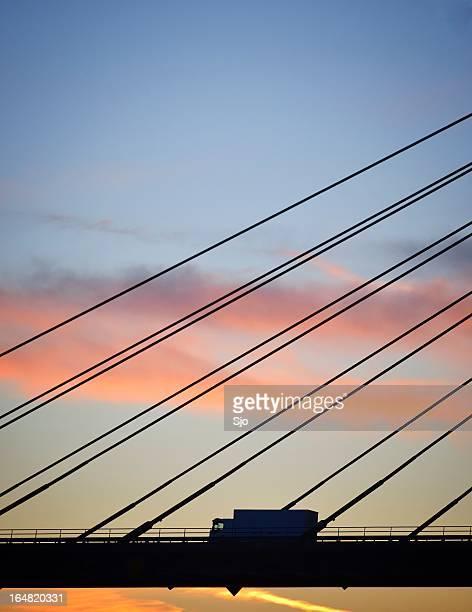 Silhouette von einem Lkw auf der Brücke bei Sonnenuntergang