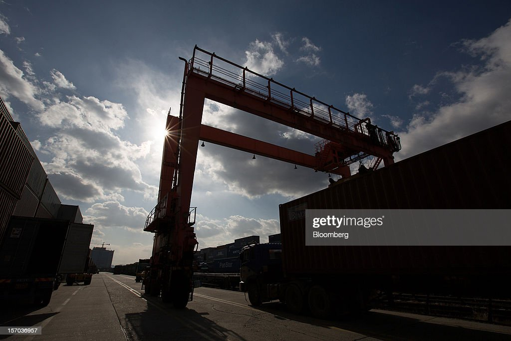 A truck sits parked below a gantry crane at the Uiwang Inland Container Depot (ICD) in Uiwang, South Korea, on Monday, Nov. 26, 2012. South Korea's current-account surplus narrowed to a two-month low after imports of machinery and equipment increased. Photographer: SeongJoon Cho/Bloomberg via Getty Images