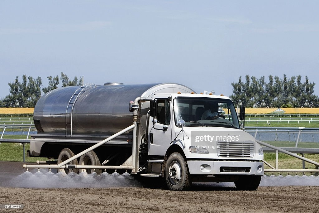 Truck spraying insecticide on crop in a field : Stock Photo