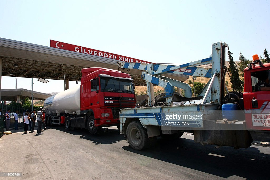 A truck towes another truck through Cilvegozu border gate which is locatd opposite of Syrian commercial crosssing point Bab al -Hava in Reyhanli Yn, in Hatay province July 21, 2012. A group of truck owners, traders and transporters who have braved Syria's highways despite the bloody conflict have been waiting since Friday at Turkey's Cilvegozu border crossing, opposite Syria's Bab al-Hawa post.