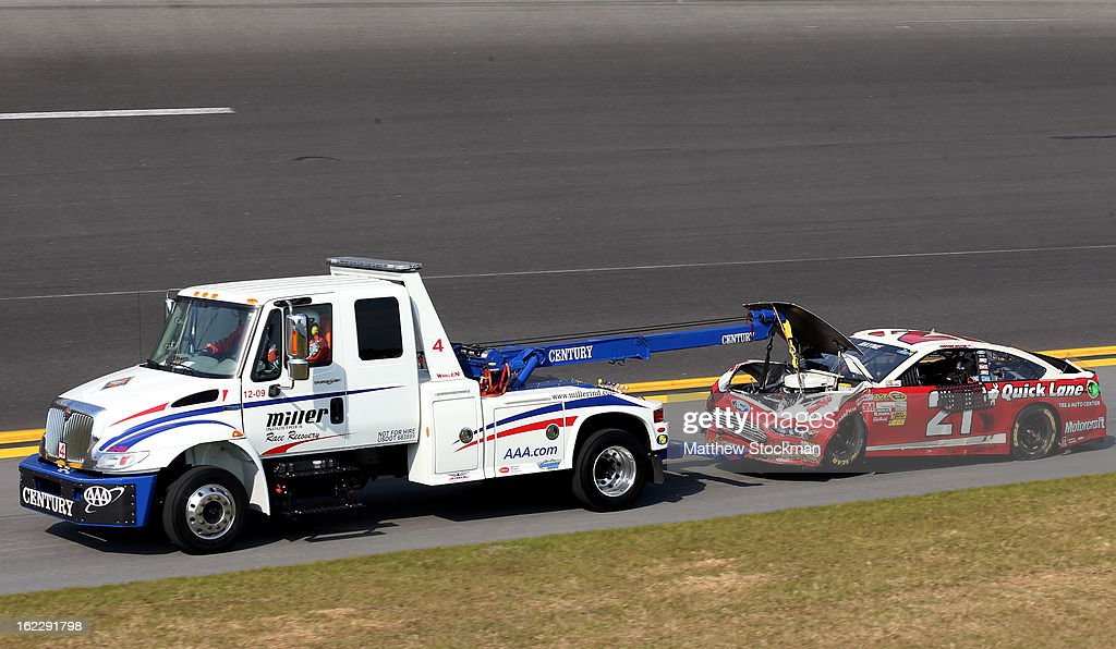 A truck tows the #21 Motorcraft/Quick Lane Tire & Auto Center Ford, driven by Trevor Bayne, after an incident in the NASCAR Sprint Cup Series Budweiser Duel 1 at Daytona International Speedway on February 21, 2013 in Daytona Beach, Florida.