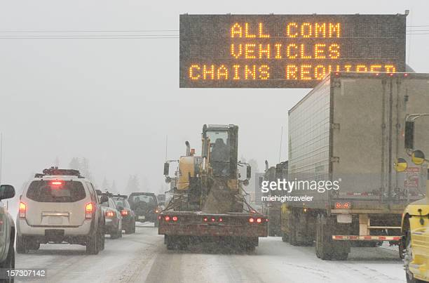 Truck traffic on I-70 highway with blizzard snow chains required