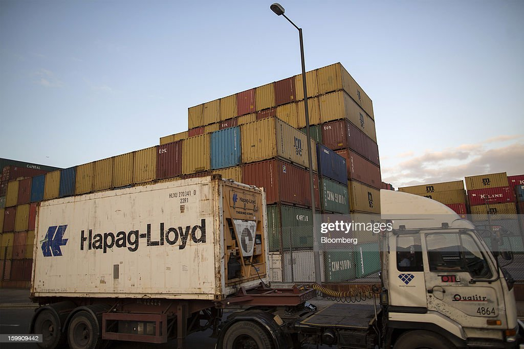 A truck transports a Hapag-Lloyd AG shipping container past stacked containers at the Kwai Tsing Container Terminals in Hong Kong, China, on Monday, Jan. 21, 2013. Hong Kong is scheduled to release export figures for December on Jan. 24. Photographer: Jerome Favre/Bloomberg via Getty Images