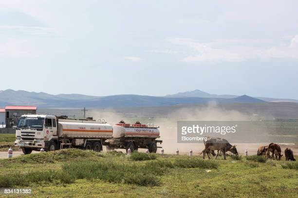 A truck travels past cars outside the Darkhan Metallurgical Plant in in Darkhan Mongolia on Monday Aug 14 2017 Mongolia desperate to make more of its...