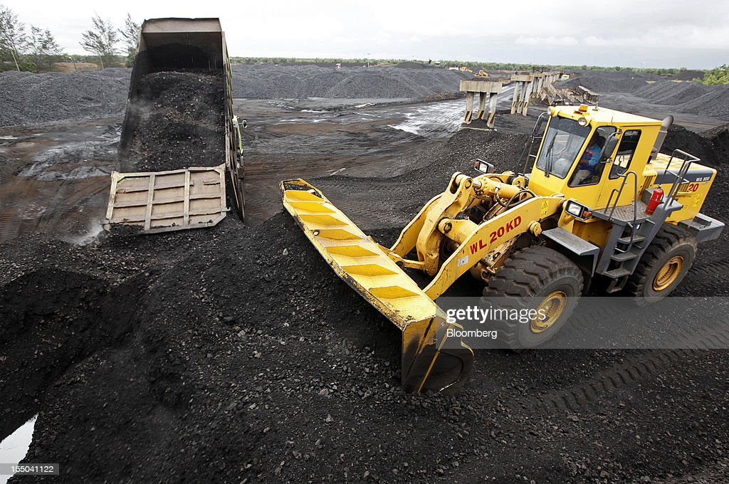 A truck unloads coal as a bulldozer forms a stockpile at the PT Exploitasi Energi Indonesia operations in Asam-Asam, South Kalimantan, Indonesia, on Monday Oct. 29, 2012. Indonesia, the world's largest exporter of coal for electricity generation, will reduce the amount of the fuel that producers must sell to buyers inside the country for next year by 9.4 percent. Photographer: Dadang Tri/Bloomberg via Getty Images