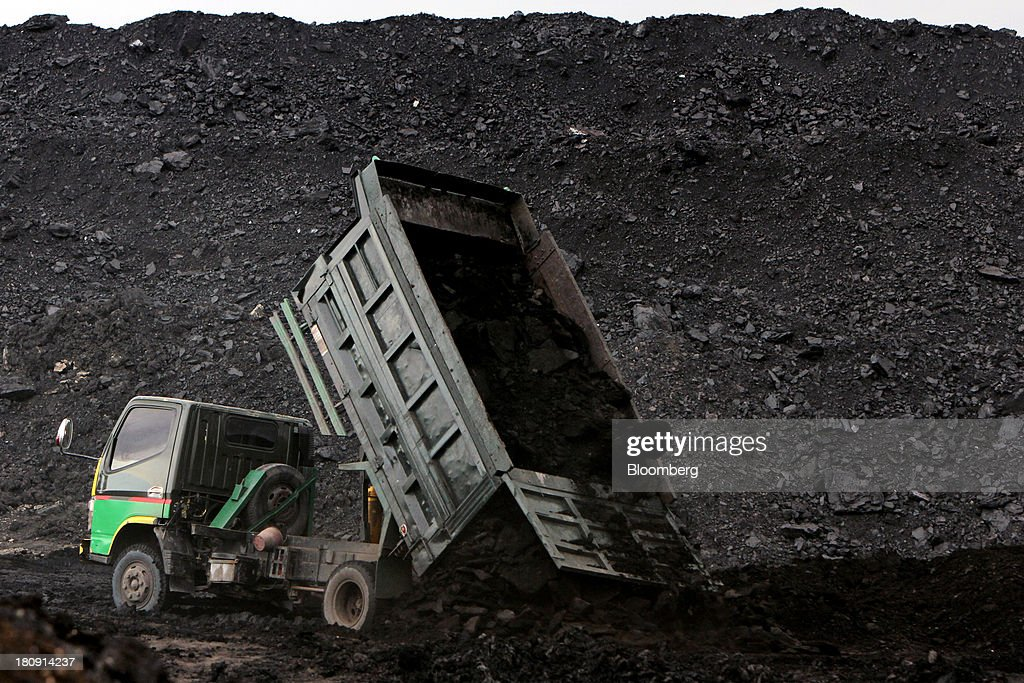 A truck unloads coal at a storage area of the PT Exploitasi Energi Indonesia open pit coal mine in Palaran, East Kalimantan province, Indonesia, on Friday, Sept. 13, 2013. Prices of power-station coal in Indonesia, the worlds biggest exporter, may be little changed in coming weeks, according to Bloomberg News survey. Photographer: Dadang Tri/Bloomberg via Getty Images