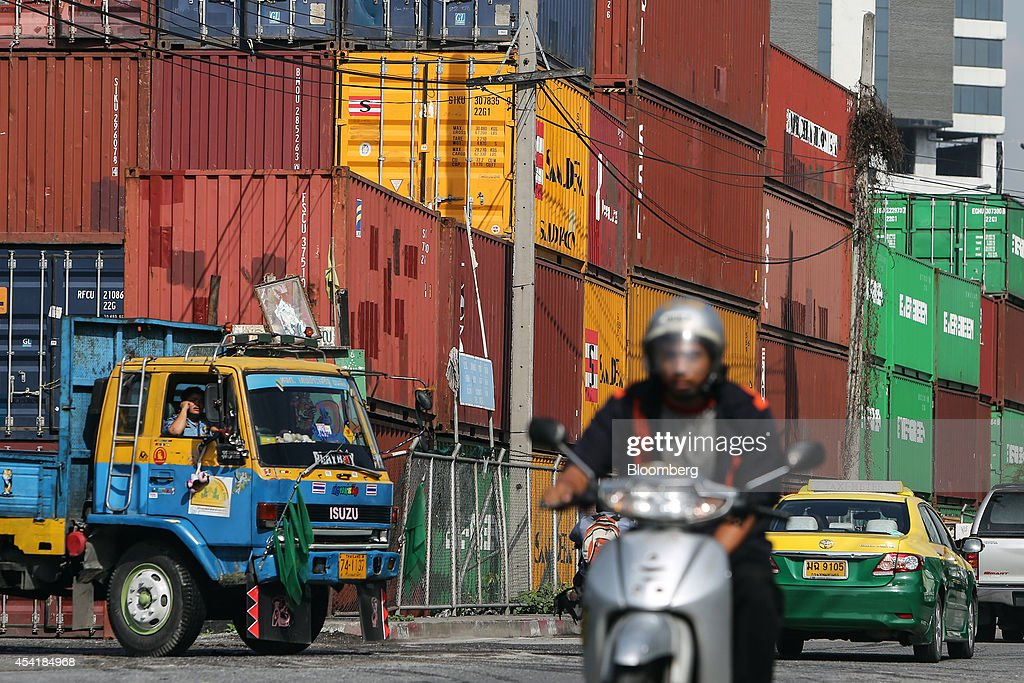 A truck waits to leave as traffic passes by containers stacked at the Custom Global Service Co. container depot in Bangkok, Thailand, on Monday, Aug. 25, 2014. Thailand's trade figures are scheduled for release on Aug. 27. Photographer: Dario Pignatelli/Bloomberg via Getty Images