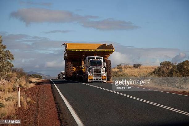 A truck with a wide load driving on a desert highway