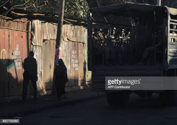 A truck with antiriot police in the back drives past closed shops with messages calling for peace painted on the doors in the Kibera district of...