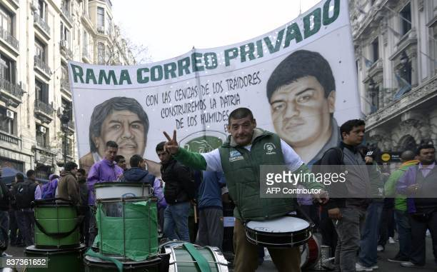 A trucker flashes the V sign in front of a large banner with the portraits of the leaders of the truck drivers union Hugo Moyano and his son Pablo...