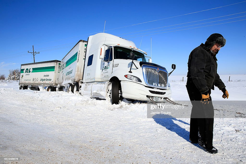 Trucker Gary Wheeler of Kansas City waits for a tow after his truck slid off the road during large midwest winter storm which brought snow throughout the region on February 22, 2013 in Greensburg, Kansas. The storm dumped at least a foot of snow in Kansas and forcasters say it is headed to the northeast U.S.