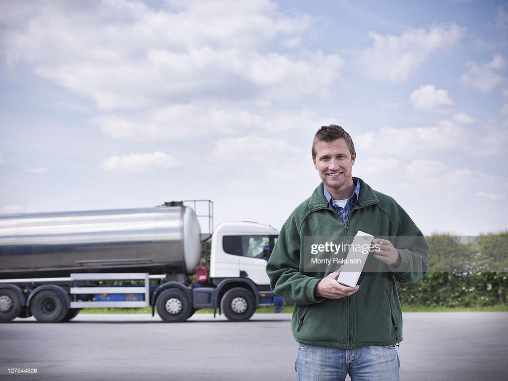 Trucker holding goat's milk by tanker