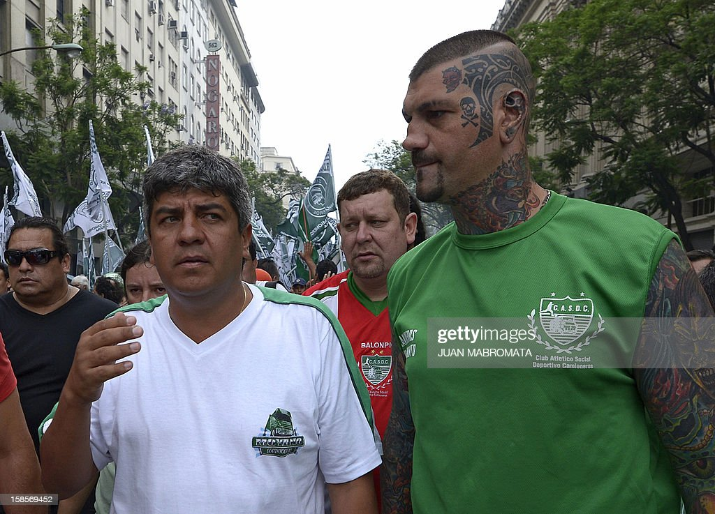 Trucker union's secretary, Pablo Moyano (L) arrives with his body guards to an anti-Government demonstration called by Union Workers (CGT), Argentine Workers Confederation (CTA), leftist parties, farmers and social organizations at Plaza de Mayo square in Buenos Aires on December 19, 2012. AFP PHOTO / Juan Mabromata