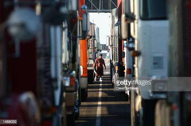 A trucker walks between rows of trucks lined up in anticipation of the reopening of the Port of Los Angeles on October 9 2002 in Los Angeles...