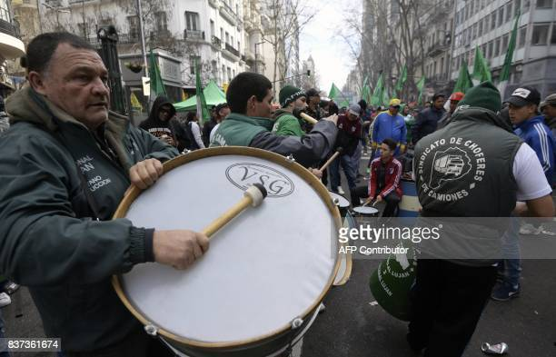 Truckers bang drums while marching toward Plaza de Mayo square in Buenos Aires on August 22 2017 during a demonstration by trade unions against the...