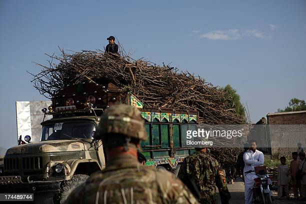 A truckload of firewood is held up as soldiers from Easy Co of the 2506th Infantry Battalion of the 4th Brigade of the 101st Airborne Division...