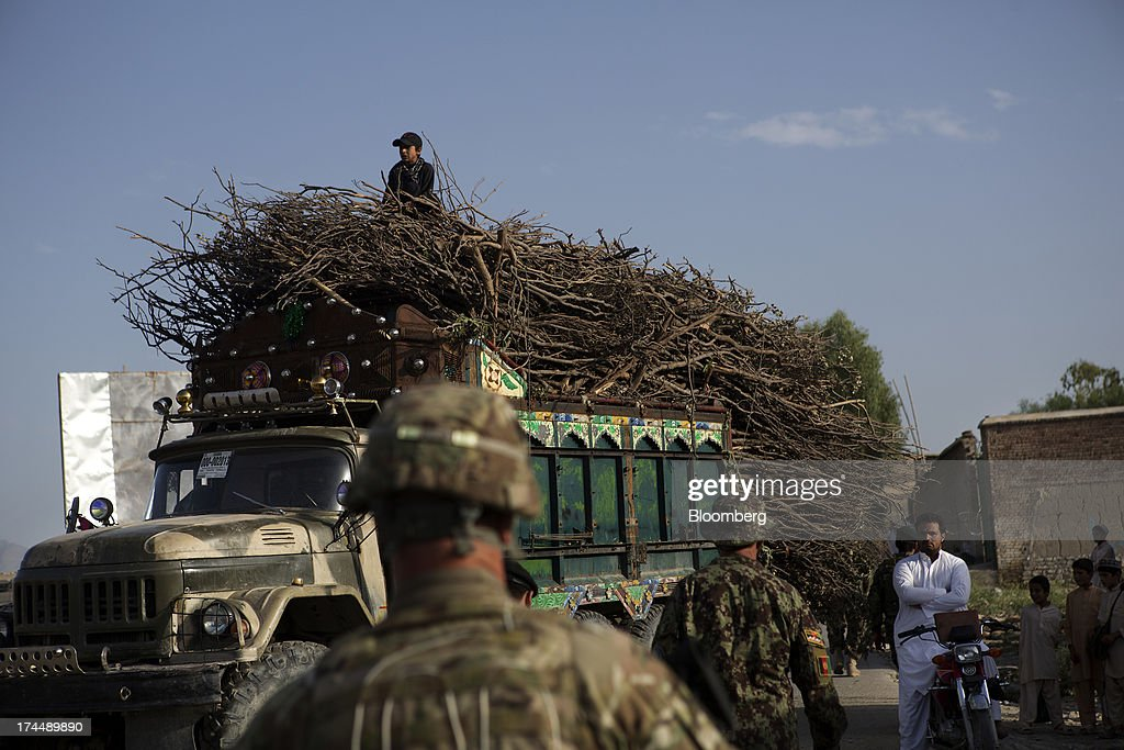 A truckload of firewood is held up as soldiers from Easy Co. of the 2-506th Infantry Battalion of the 4th Brigade of the 101st Airborne Division conduct a mission with the Afghan National Army and Police in the remote Musa Khel district of Khost province, Afghanistan, on Wednesday, July 3, 2013. U.S. President Barack Obama has maintained his position of ending U.S. combat in Afghanistan by the end of next year, though that plan has included keeping in place several thousand troops for support. Photographer: Victor J. Blue/Bloomberg via Getty Images