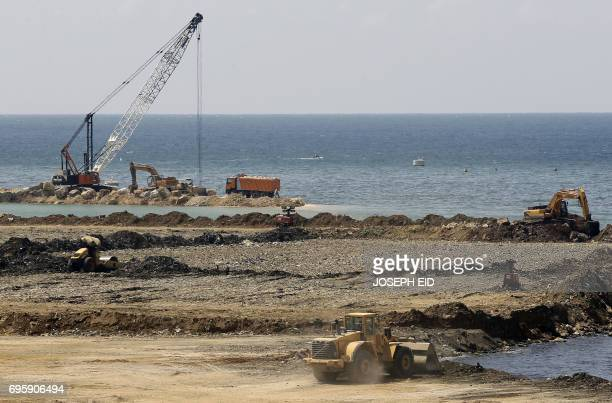 Trucks and bulldozers tip rubbish into the Mediterranean Sea at Borj Hammoud on the northern outskirts of the Lebanese capital Beirut on June 14 2017...