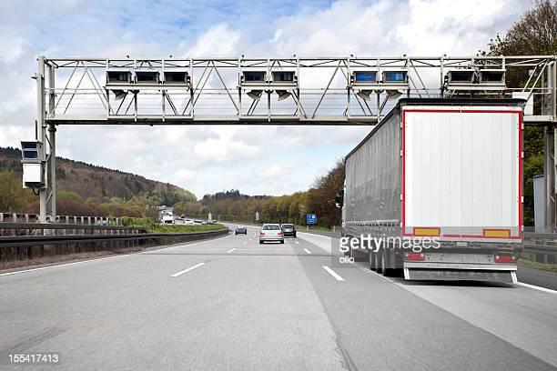 Lastwagen mit Autos auf Deutsch highway, Mautsystem gantry