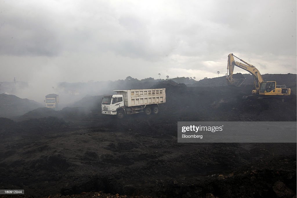 Trucks and excavators operate in the smoke at the PT Exploitasi Energi Indonesia open pit coal mine in Palaran, East Kalimantan province, Indonesia, on Friday, Sept. 13, 2013. Prices of power-station coal in Indonesia, the worlds biggest exporter, may be little changed in coming weeks, according to Bloomberg News survey. Photographer: Dadang Tri/Bloomberg via Getty Images