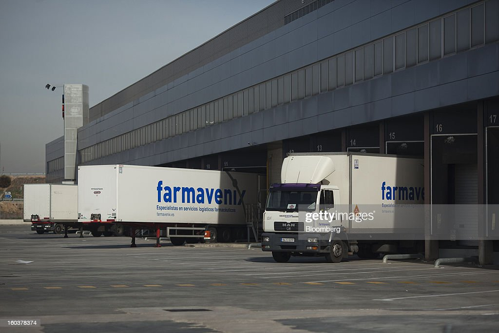Trucks and trailers stand at the Farmavenix distribution depot, part of the Cofares SA plant in Guadalajara, Spain, on Wednesday, Jan. 30, 2013. Madrid, the second-biggest contributor to Spain's economy after Catalonia, has sliced 1 billion euros from its budget in 2012, increasing public-transportation costs and university fees, cutting jobs, delaying investments and reducing health-care and social benefits. Photographer: Angel Navarrete/Bloomberg via Getty Images