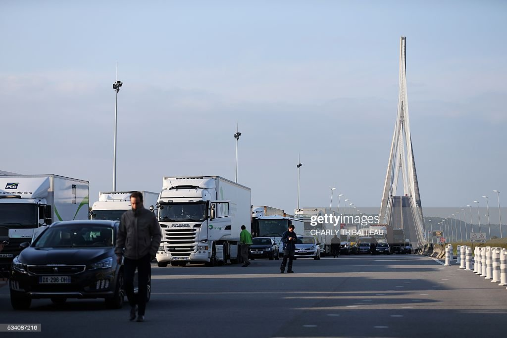 Trucks are at a standstill as unionists block the tollgate of the 'Pont de Normandie', in Le Havre northwestern France, on May 25, 2016, to protest against the government's proposed labour reforms. Refinery workers stepped up strikes that threaten to paralyse France weeks ahead of the Euro 2016 tournament as the government moved to break their blockades, escalating a three-month tug-of-war over labour reforms. / AFP / CHARLY