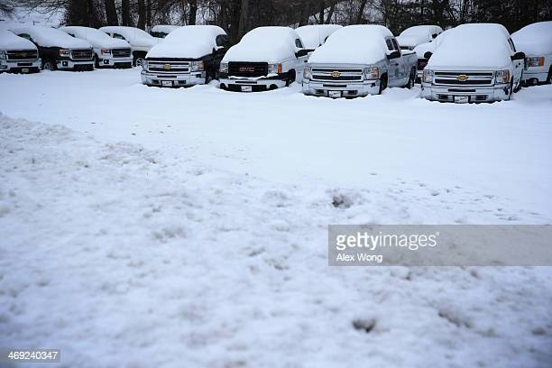 Trucks are covered with snow as they sit in a car dealer lot February 13 2014 in Warrenton Virginia The Washington DC area is embracing the biggest...