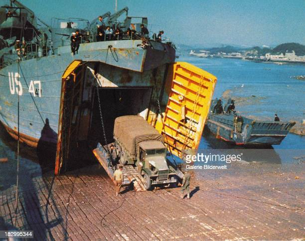 Trucks are loaded into a Landing Ship Tank in Southern England United Kingdom for the invasion of Normandy June 1944 The ship was beached at Omaha...