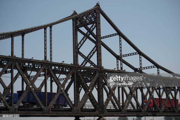 Trucks are seen crossing the Friendship Bridge from North Korea's Sinuiju over to the Chinese border city of Dandong over the Yalu river in the...