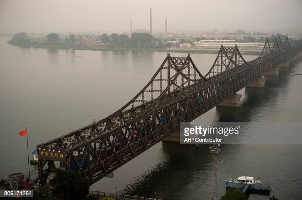 Trucks are seen crossing the Friendship Bridge from the Chinese border city of Dandong to North Korea's Sinuiju over the Yalu river in the Chinese...
