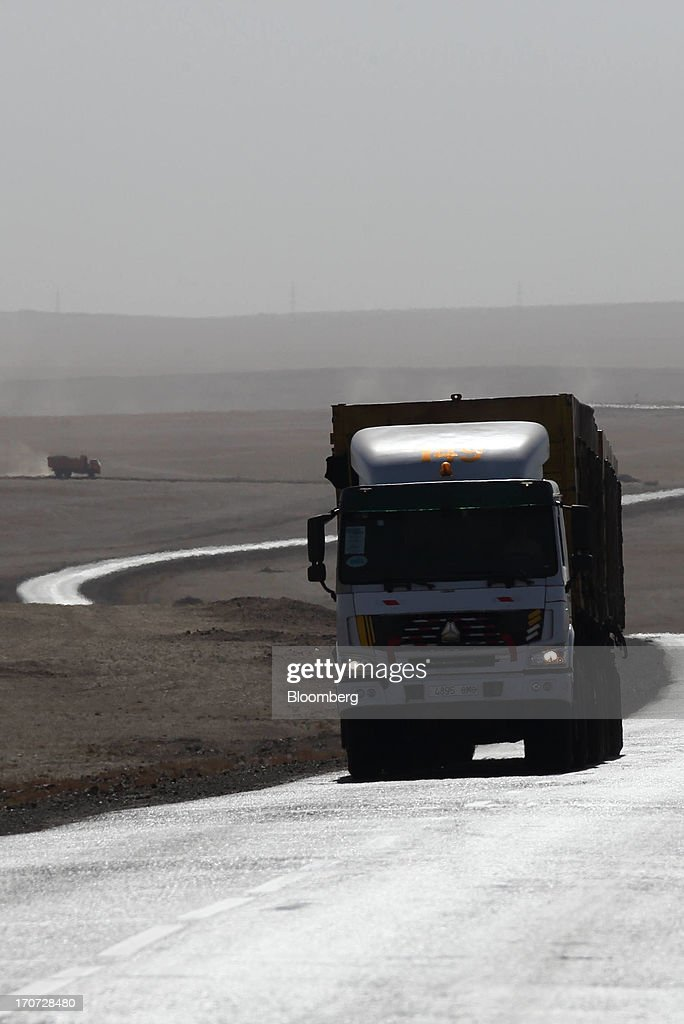 Trucks carry coal along a paved road leading to the border with China in South Gobi, Mongolia, on Thursday, June 6, 2013. Mongolia, a country of almost 2.9 million people, has some of the world's biggest undeveloped mineral reserves, including Oyu Tolgoi, a copper and gold mine, and Tavan Tolgoi, a coal deposit. Photographer: Tomohiro Ohsumi/Bloomberg via Getty Images