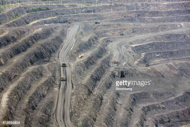Trucks carry excavated iron ore from the open pit of the Lebedinsky GOK iron ore mining and processing plant operated by MetalloinvestHolding Co in...