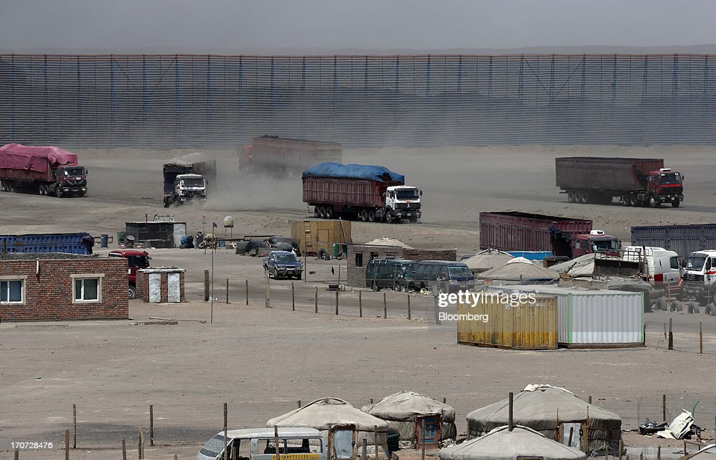 Trucks carrying coal drive in front of a reloading facility on the border with China in South Gobi, Mongolia, on Thursday, June 6, 2013. Mongolia, a country of almost 2.9 million people, has some of the world's biggest undeveloped mineral reserves, including Oyu Tolgoi, a copper and gold mine, and Tavan Tolgoi, a coal deposit. Photographer: Tomohiro Ohsumi/Bloomberg via Getty Images