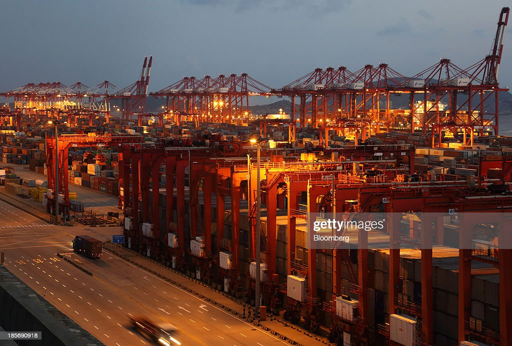 Trucks carrying containers drive through the Yangshan Deep Water Port, part of China (Shanghai) Pilot Free Trade Zone's Yangshan free trade port area, at night in Shanghai, China, on Wednesday, Oct. 23, 2013. The area is a testing ground for free-market policies that Premier Li Keqiang has signaled he may later implement more broadly in the world's second-largest economy. Photographer: Tomohiro Ohsumi/Bloomberg via Getty Images