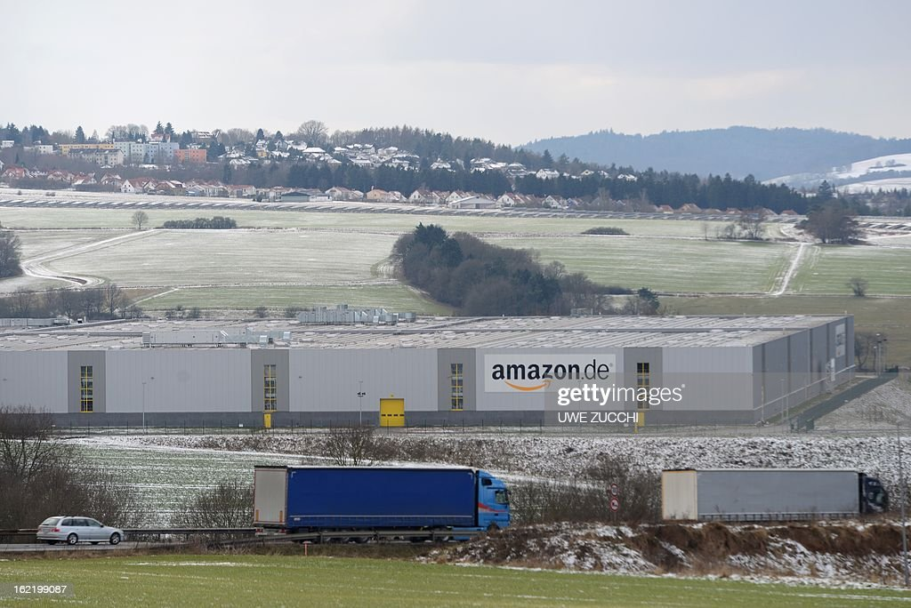 Trucks drive in front of the German logistics center of online retailer Amazon in Bad Hersfeld, western Germany on February 20, 2013. The German competition watchdog on Wednesday, February 20, 2013 launched an investigation into the policy of online retailer Amazon which bans third-party traders from selling their products cheaper elswhere on the web. AFP PHOTO / UWE ZUCCHI GERMANY OUT