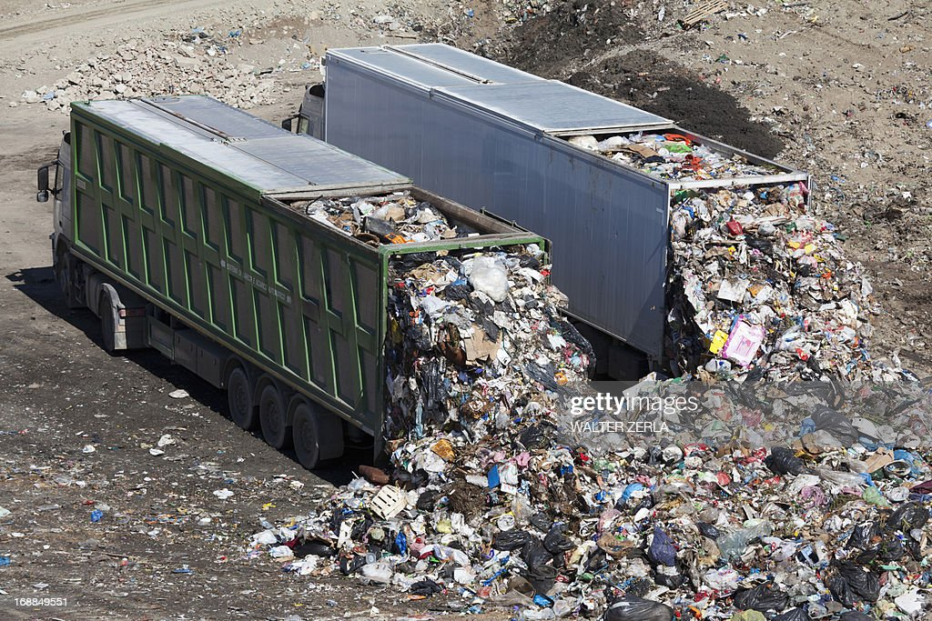 Trucks dumping waste in landfill