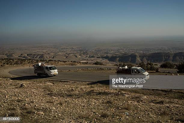 Trucks filled with appliances are seen driving out of Sinjar
